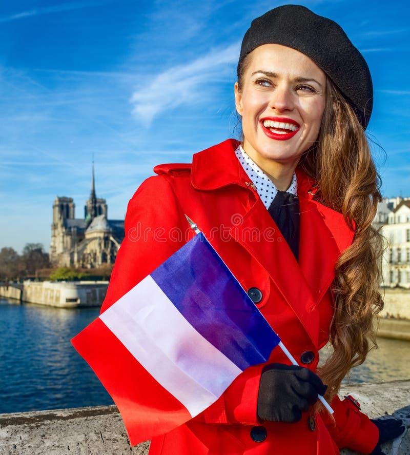 Femme de sourire à Paris avec le drapeau français examinant le distanc photos stock