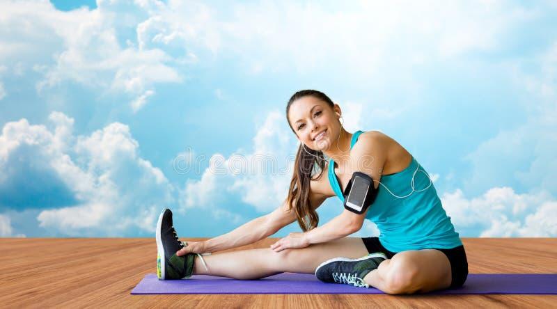 Femme de sourire étirant la jambe sur le tapis au-dessus des nuages images stock
