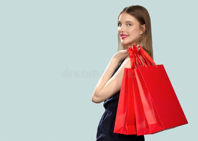 Femme de sourire de achat de mode tenant les paquets rouges images libres de droits