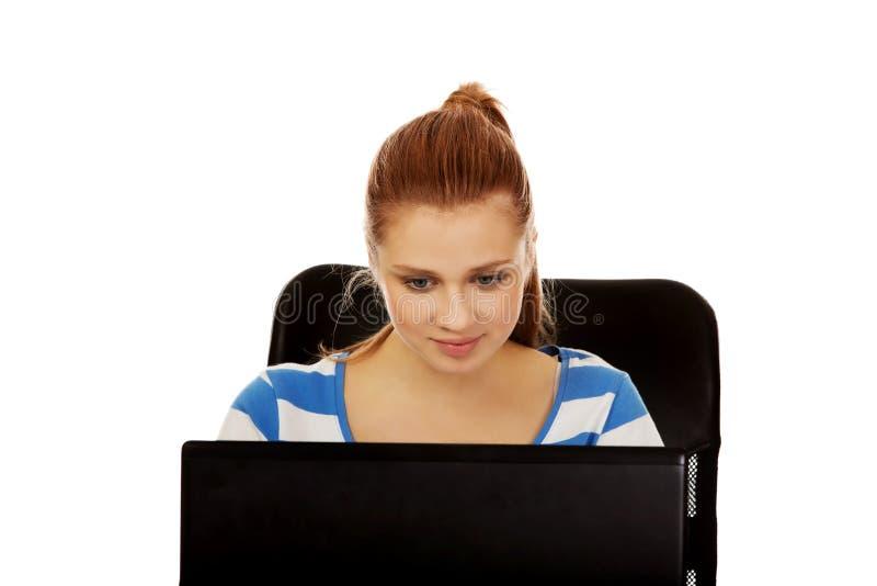 Femme de sourire adolescente à l'aide de l'ordinateur portable image stock
