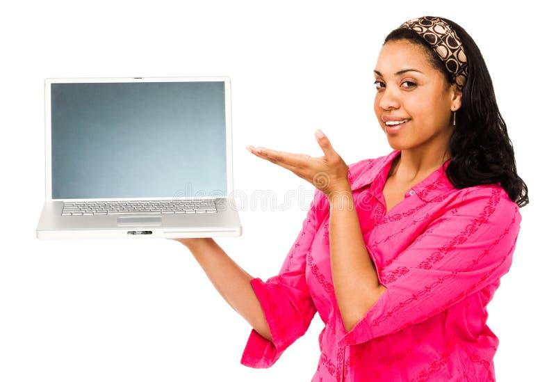 Femme de sourire affichant l'ordinateur portatif photographie stock