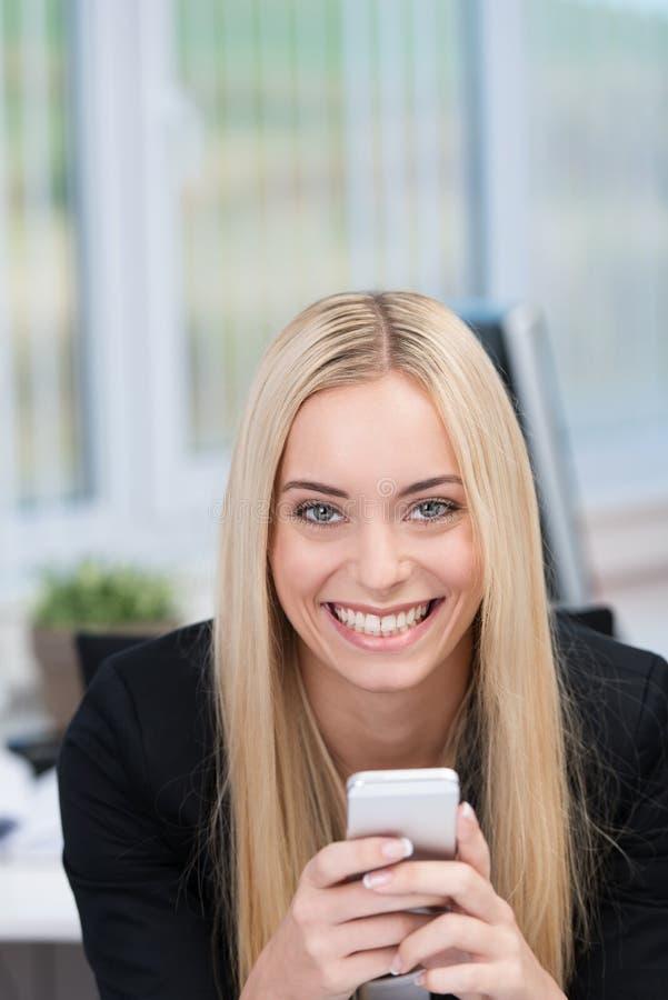 Femme de sourire amicale avec un téléphone portable photographie stock libre de droits