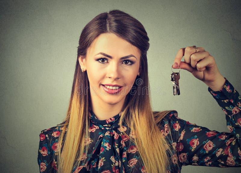 Femme de sourire attirante de portrait retardant l'ensemble de clés appartenant à sa maison ou voiture photos stock
