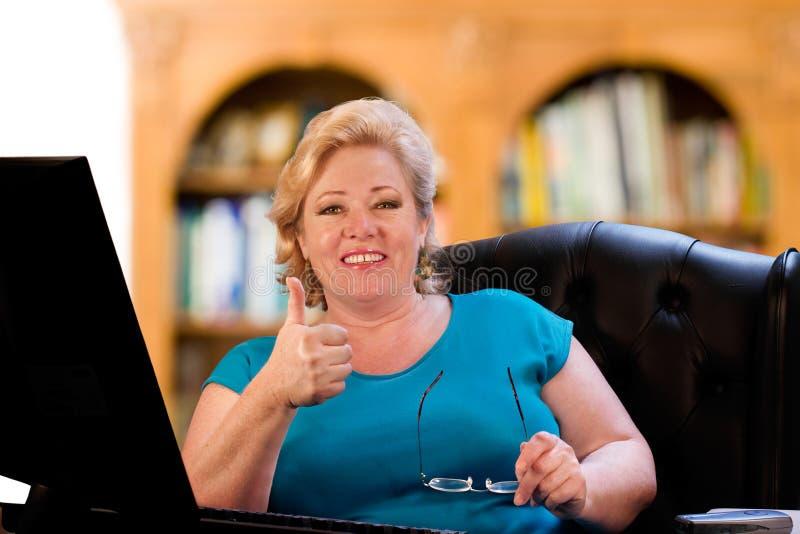 Femme de sourire au bureau images libres de droits