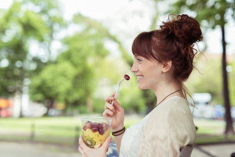 Femme de sourire au parc mangeant de la salade de fruit frais image libre de droits