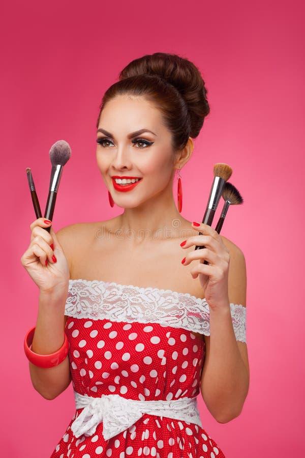 Femme de sourire avec des brosses de maquillage Elle se tient image stock
