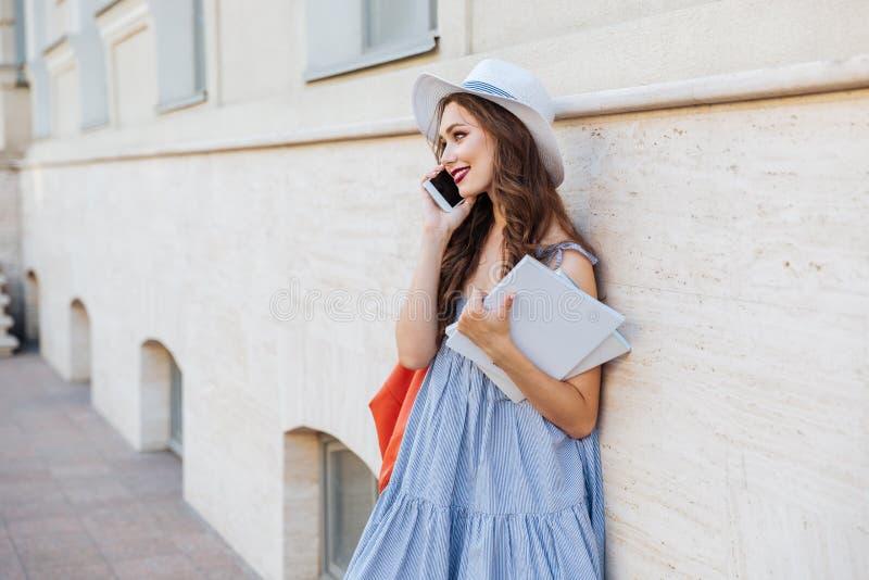 Femme de sourire avec des livres se tenant et parlant au téléphone portable photo stock