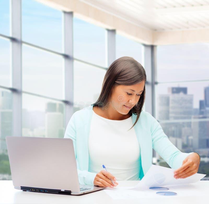 Femme de sourire avec l'ordinateur portable et les papiers photo libre de droits