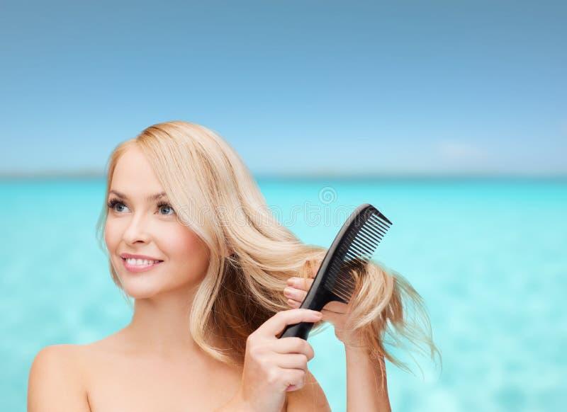 Femme de sourire avec la brosse de cheveux images libres de droits