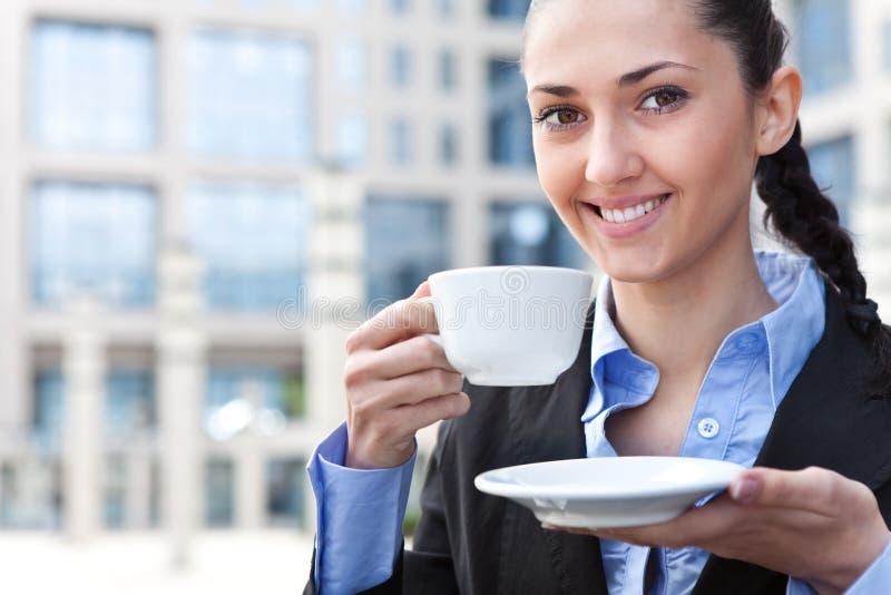 Femme de sourire avec la cuvette de café image stock