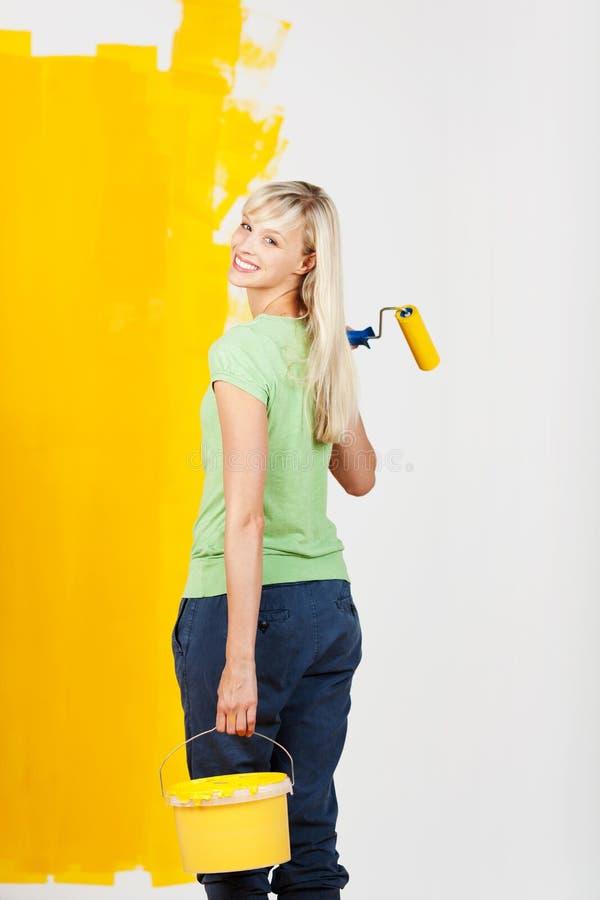 Femme de sourire avec la peinture jaune et un rouleau photo libre de droits