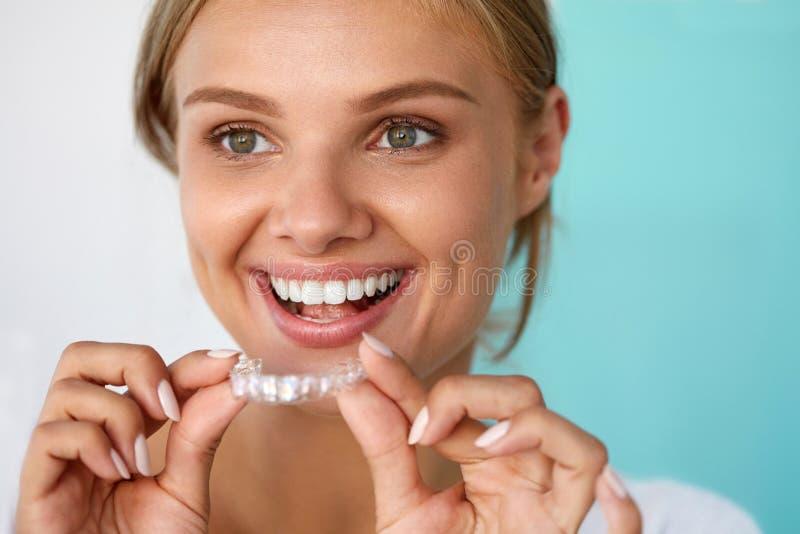 Femme de sourire avec le beau sourire utilisant des dents blanchissant le plateau photo stock