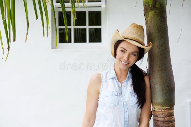Femme de sourire avec le chapeau de cowboy se penchant contre l'arbre photos stock