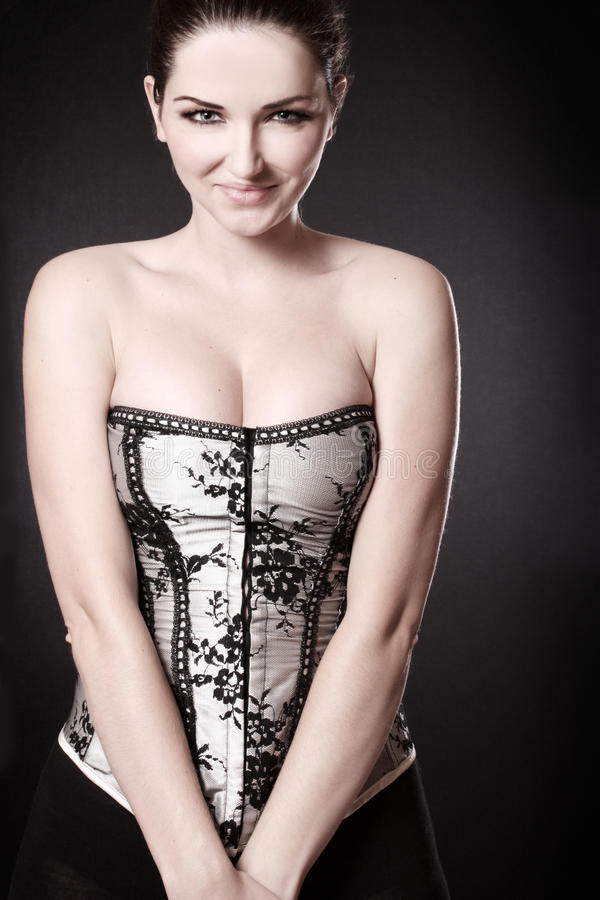 Femme de sourire avec le fendage dans un corset photo stock