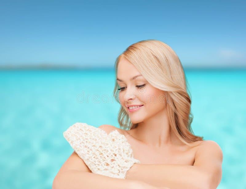 Femme de sourire avec le gant d'exfoliation image stock