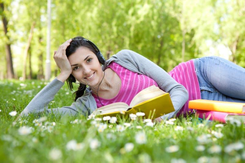 Femme de sourire avec le livre en nature photographie stock libre de droits