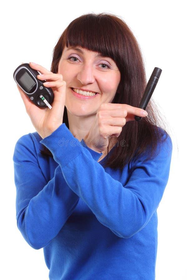 Femme de sourire avec le mètre de glucose sur le fond blanc photographie stock libre de droits
