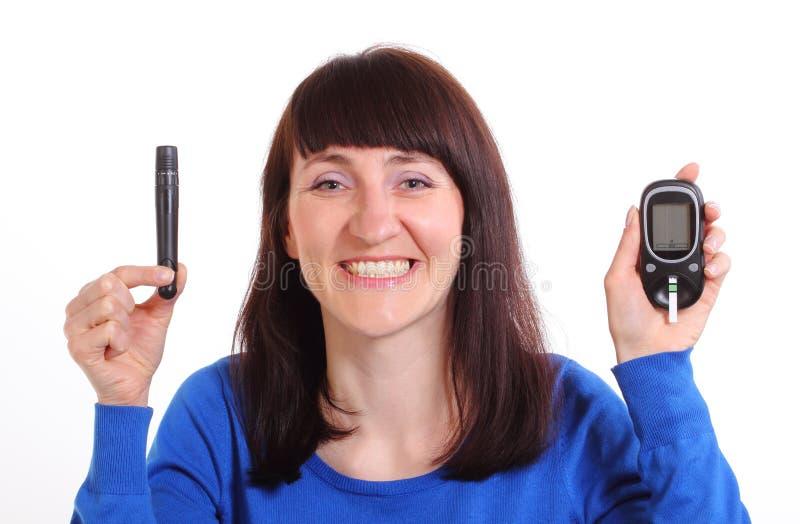 Femme de sourire avec le mètre de glucose sur le fond blanc photos stock