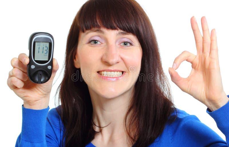 Femme de sourire avec le mètre de glucose sur le fond blanc image libre de droits