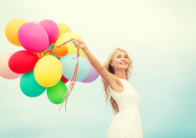 Femme de sourire avec les ballons colorés dehors image stock
