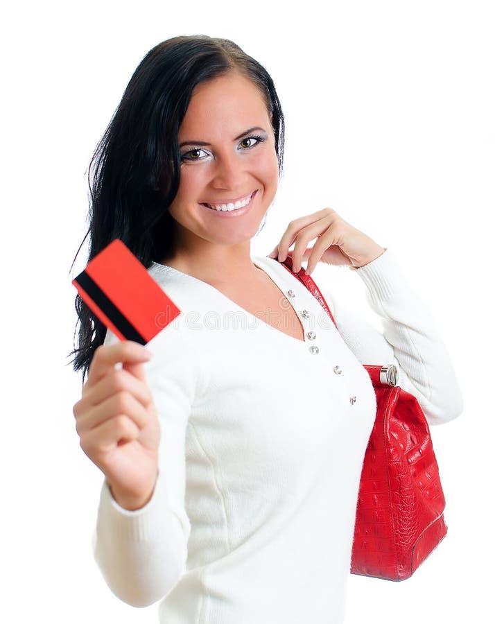 Femme de sourire avec par la carte de crédit rouge photo stock