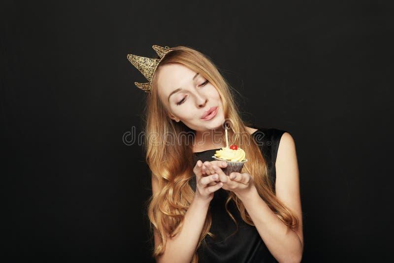 Femme de sourire, avec une couronne, tenant un petit gâteau d'anniversaire photo libre de droits