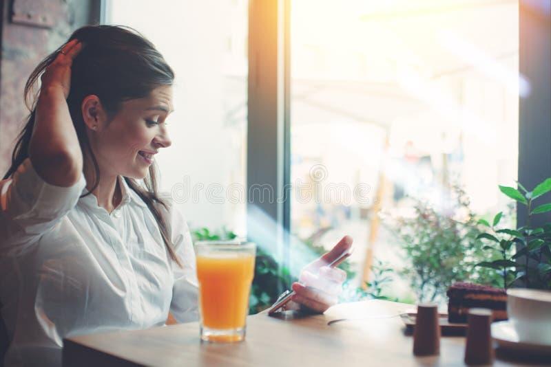 Femme de sourire belle avec le téléphone portable se reposant en café, textotant dans les réseaux sociaux photos stock
