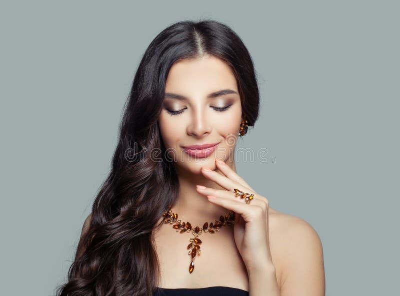 Femme de sourire de brune avec la longue coupe de cheveux onduleuse, le maquillage et le collier d'or, portrait de mode photographie stock