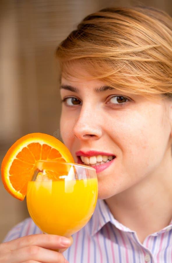 Femme de sourire buvant du jus d'orange images libres de droits
