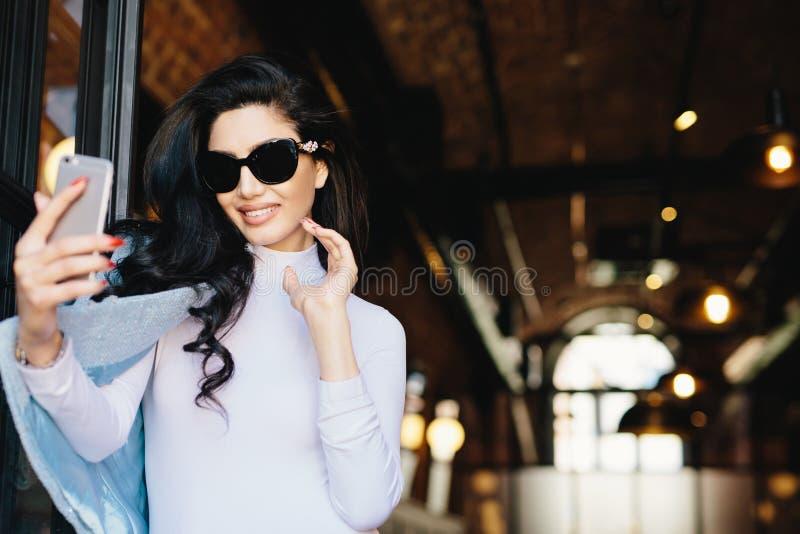 Femme de sourire de charme dans les lunettes de soleil, le chemisier blanc et la position de veste photo stock