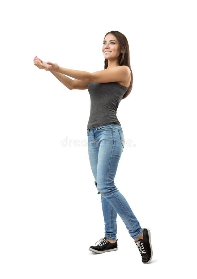 Femme de sourire convenable de jeunes dans le dessus sans manche gris et blues-jean se tenant dans le moitié-tour donnant ses mai photographie stock