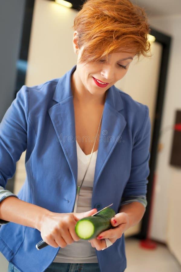 Femme de sourire coupant les légumes frais photo libre de droits