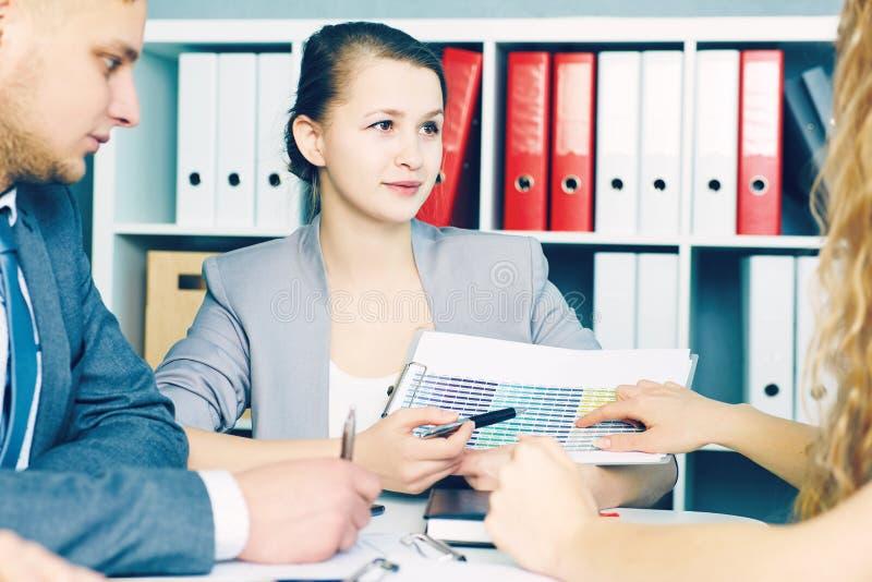Femme de sourire d'affaires avec le presse-papiers indiquant le stylo le diagramme au bureau Affaires, les gens, statistiques et  photos stock