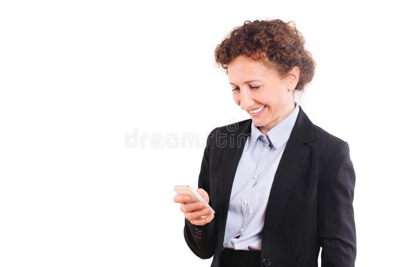 Femme de sourire d'affaires dans le costume tenant le smartphone et regardant là-dessus image stock