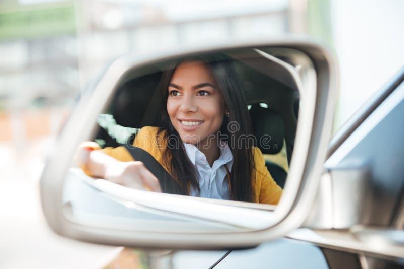 Femme de sourire d'affaires dans le miroir de voiture de vue de côté photo stock