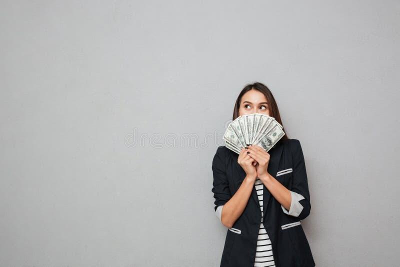 Femme de sourire d'affaires se cachant derrière l'argent et regardant loin photographie stock libre de droits