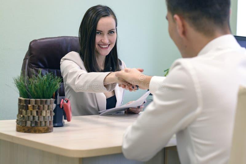 Femme de sourire d'affaires serrant la main à un jeune homme d'affaires au bureau dans le bureau Le concept de l'entrevue, accord images stock