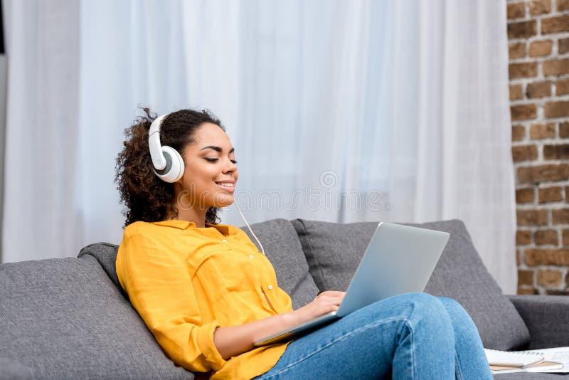 femme de sourire d'afro-américain travaillant avec l'ordinateur portable et la musique de écoute sur le divan photos libres de droits