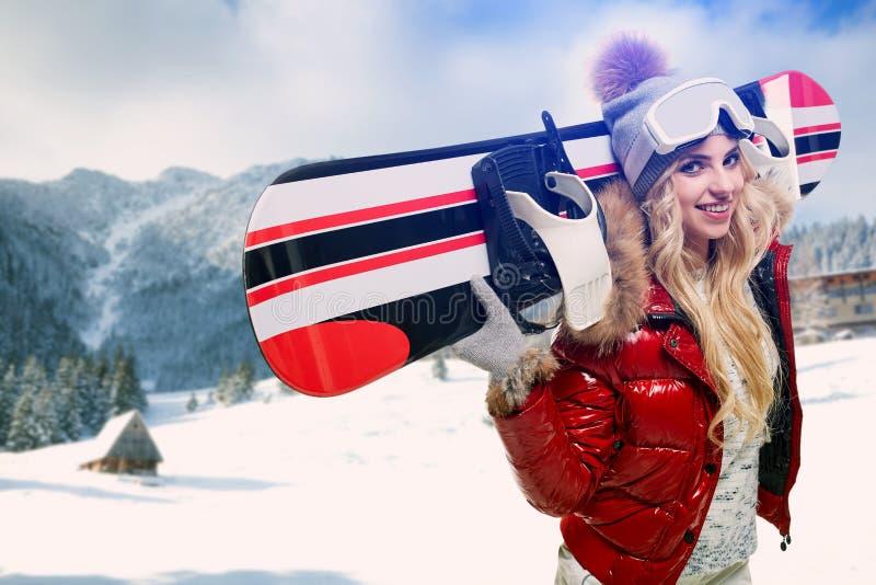 Femme de sourire d'hiver avec le surf des neiges image libre de droits