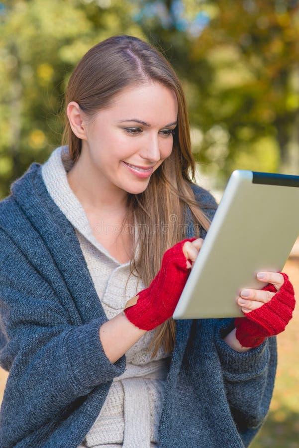 Download Femme De Sourire Dans Des Mitaines Rouges Utilisant Un Comprimé Photo stock - Image du sain, tablette: 45355422