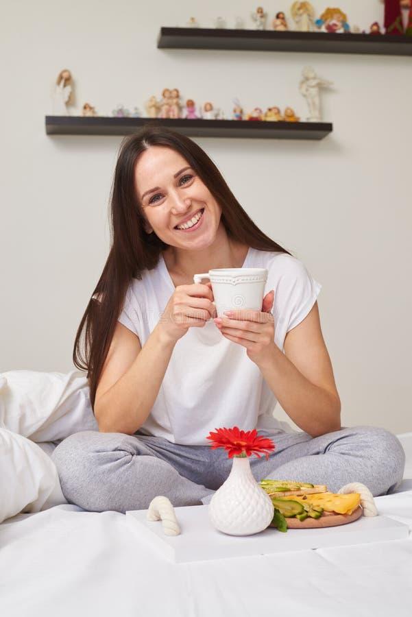 Femme de sourire dans des pyjamas appréciant le petit déjeuner romantique photographie stock libre de droits