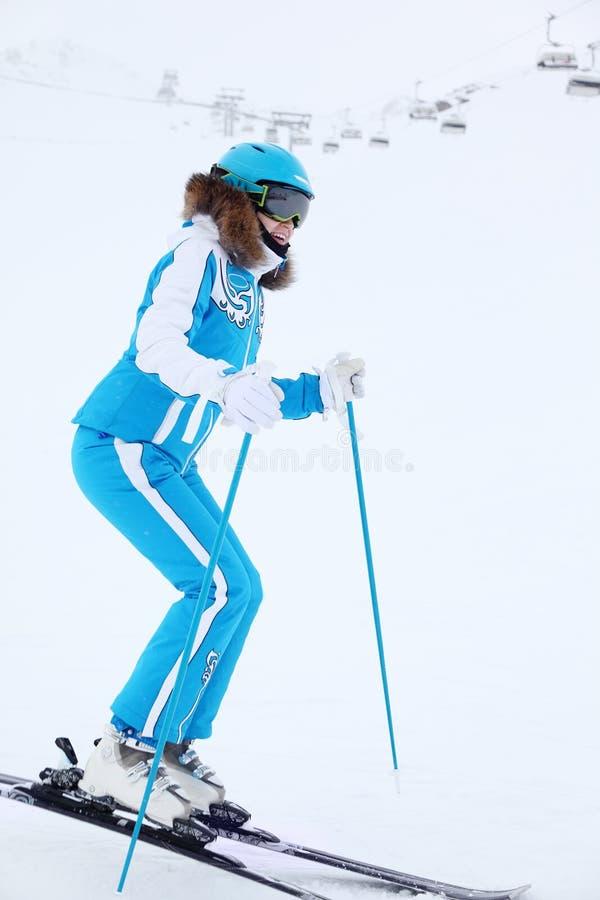 Femme de sourire dans des skis de casque à l'hiver image stock