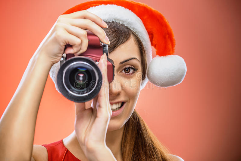 Femme de sourire dans des vêtements de Santa Claus avec l'appareil-photo image stock