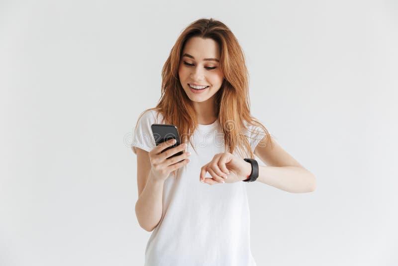 Femme de sourire dans des vêtements sport avec la montre-bracelet utilisant le smartphone photos stock