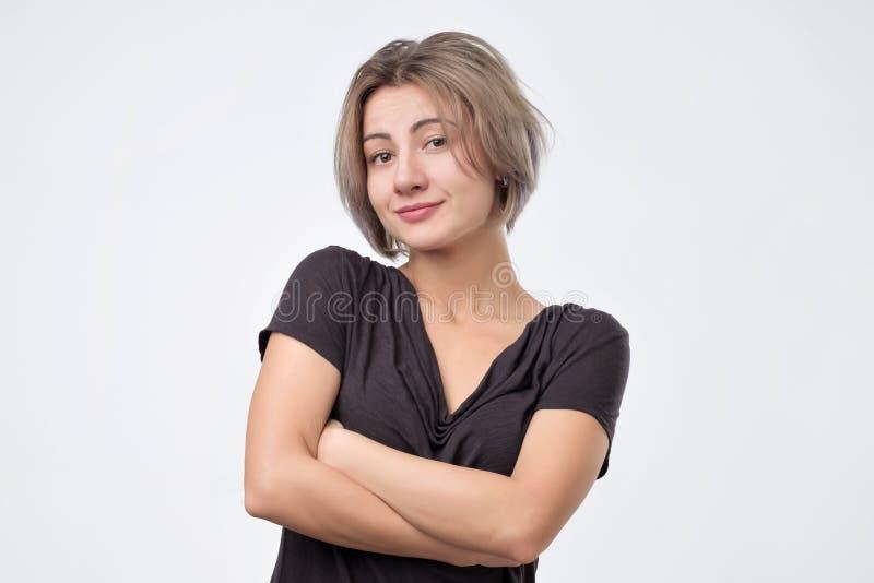 Femme de sourire dans la chemise noire avec les bras croisés regardant et sourire images stock