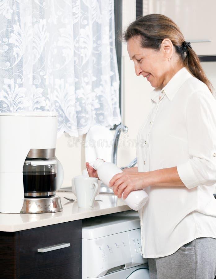 Femme de sourire dans la cuisine photographie stock libre de droits