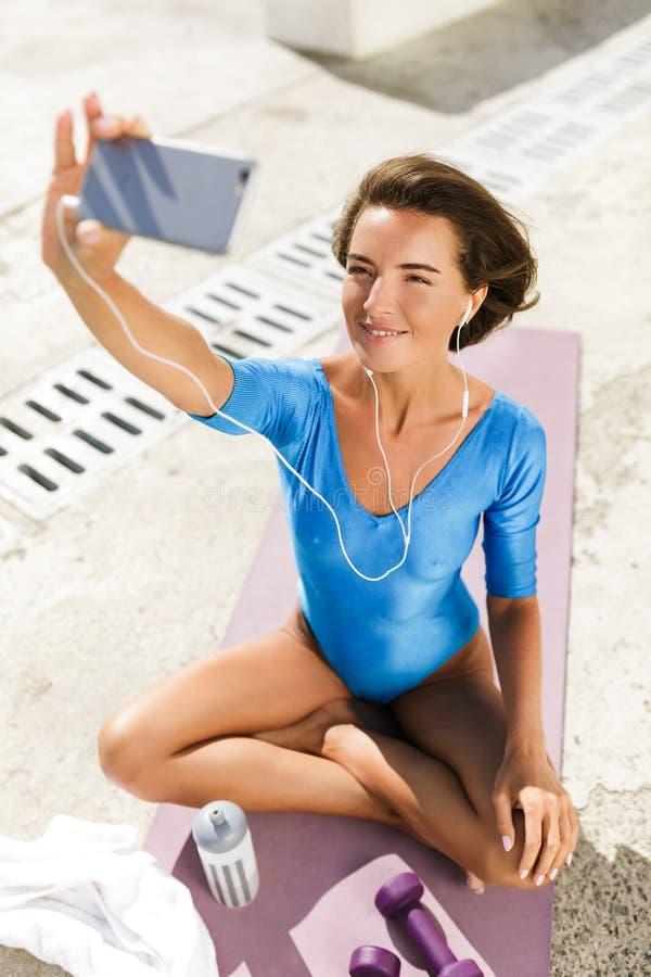 Femme de sourire dans le maillot de bain se reposant sur le tapis de yoga regardant heureusement le téléphone portable et en pren photographie stock