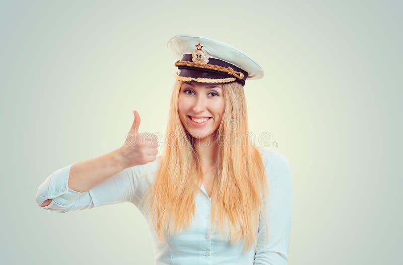 Femme de sourire dans le pouce d'apparence de chapeau de fourrage de marine  photos libres de droits
