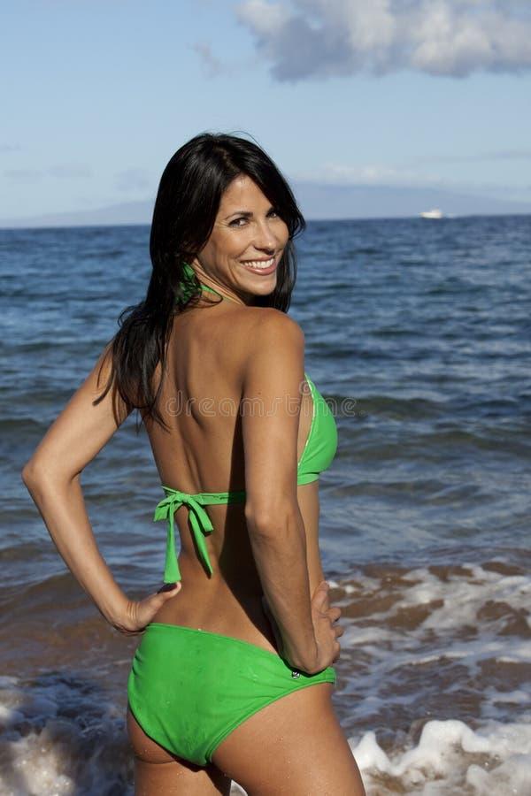 Femme de sourire dans un bikini vert photographie stock