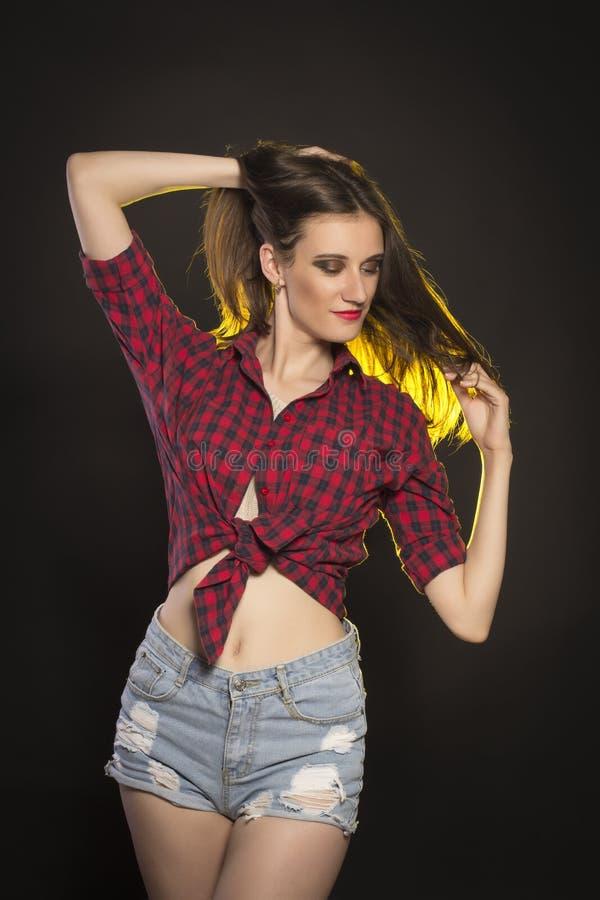 Femme de sourire de brune dans les shorts de jeans et la chemise de plaid image libre de droits